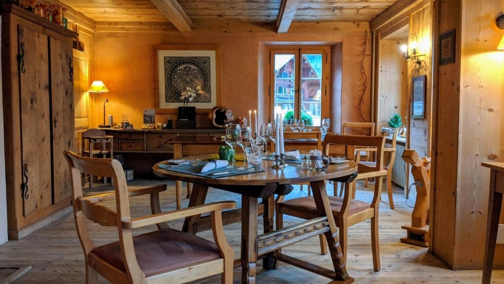 Dining room at Restaurant les jardins de la tour in Rossinière, Pays-d'Enhaut, Switzerland. The picutre shows the dining room. In front the wooden chairs and dining table.