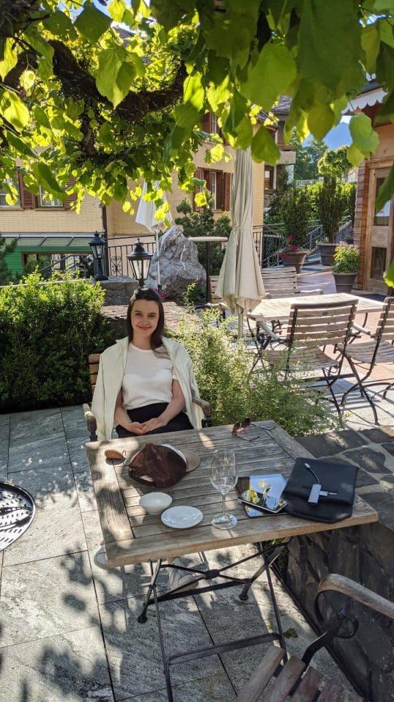 Solène sitting at the table on the terrace of hotel Schönegg in Wengen, Switzerland.