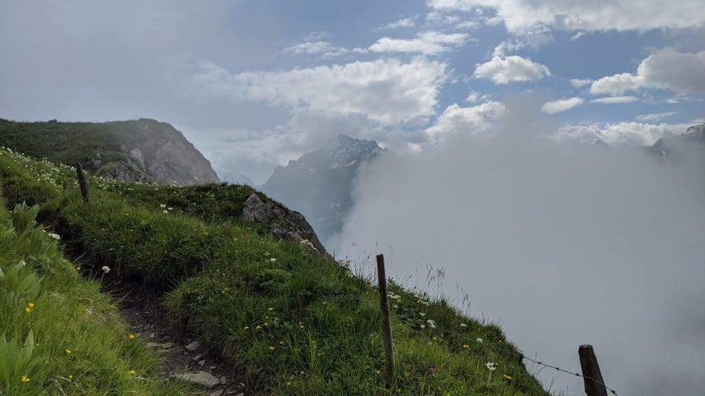 Hiking trail above the clouds on the Via Alpina from Kandersteg to Adelboden over Bunderchrine mountain pass.