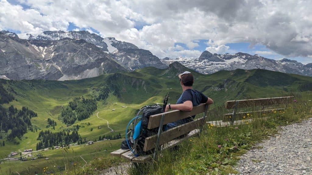 Matthias looking at Wildstrubel mountain from Flowertrail in Adelboden, Switzerland. Below him Gleis and the Via Alpina trail.