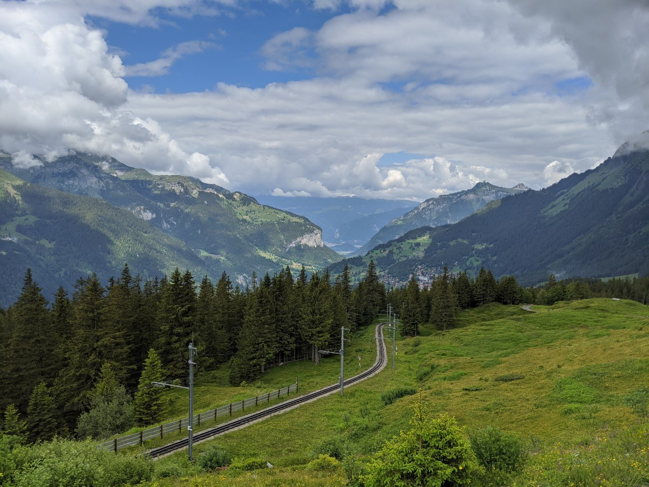 View from the Via Alpina hiking trail to Wengen, Switzerland. On it the track of the Wengernalpbahn railway. In the background a view of Lauterbrunnen valley.