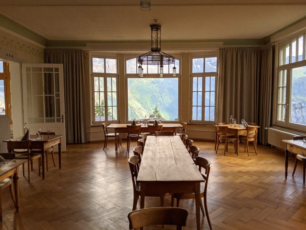 The Dining hall at hotel Regina in Mürren with views to Jungfrau massif.