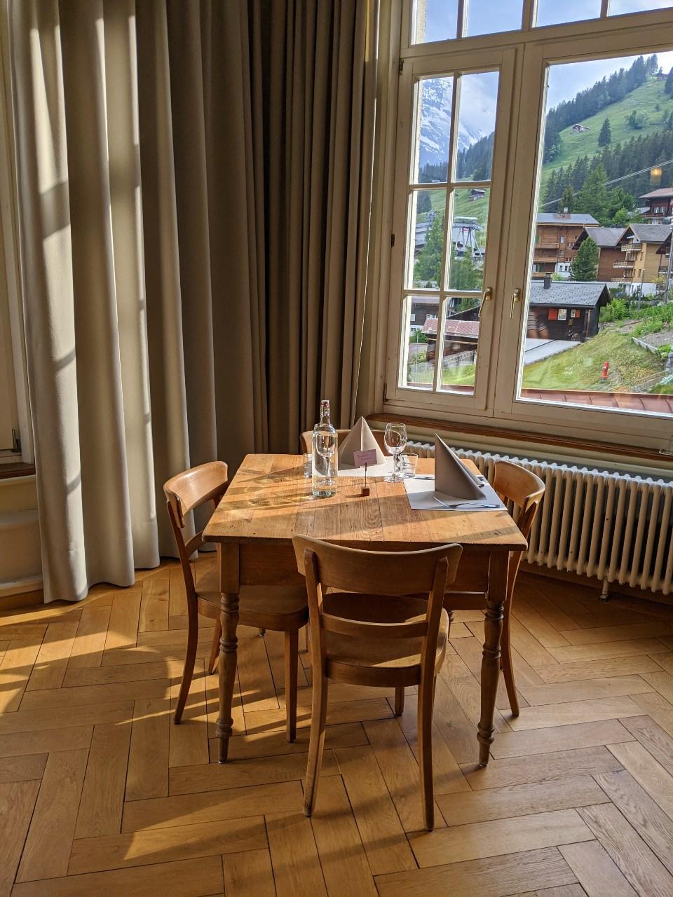 Dining table in hotel Regina in Mürren. Last sunbeams of the day caressing the wooden floor.
