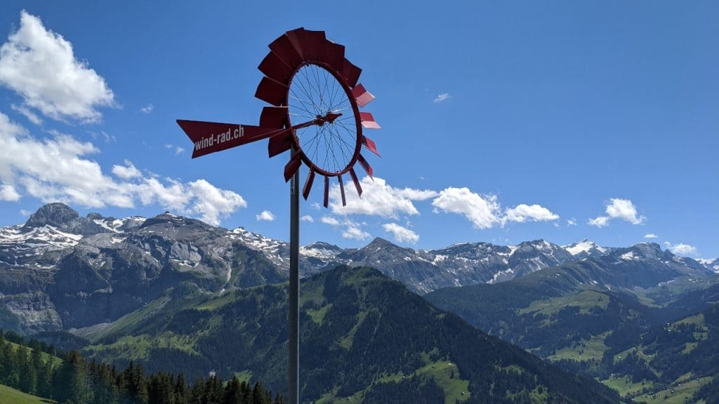 Windmill at restaurant Buehlberg in Lenk, Simmental. Behind it the iconic mountain Wildstrubel, glacier Plaine morte and the Truettlisberg mountain pass.