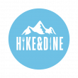 Hike&Dine Logo in white letters on blue background. Above the letters a mountain in white.